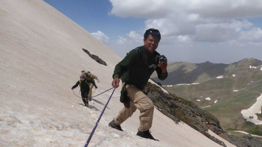Zau Seng crosses the snow field, camera in hand.