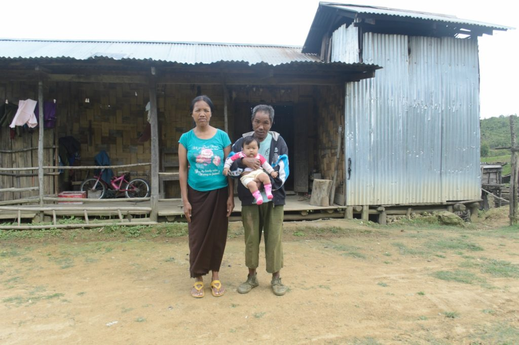 Local family outside their corrugated metal dwelling, Falam township, Chin state.