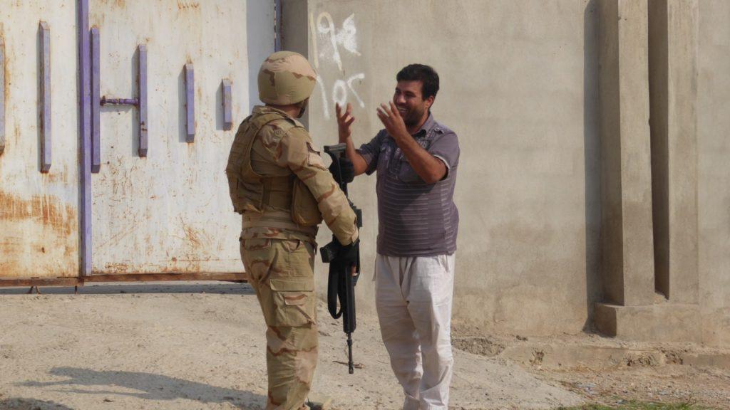 Man in Faizalia thanks a Kurd soldier.