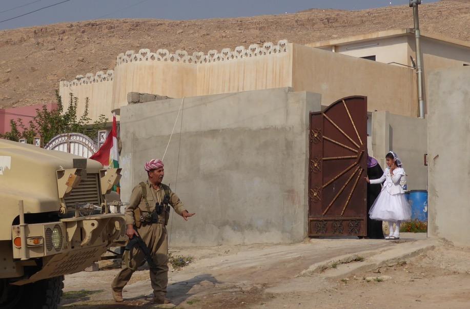 Girl watches as Kurd column enters Faizalia.