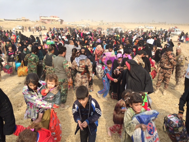 IDPs stream through the breach after being liberated from ISIS control.