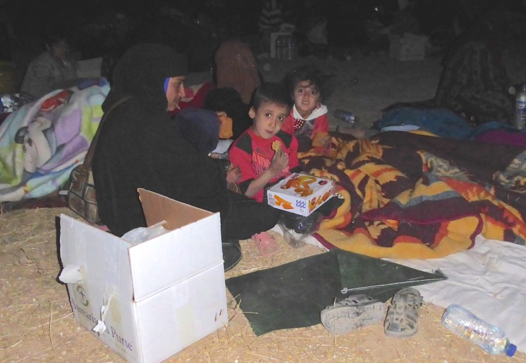 A family huddles around a distributed food box given by Samaritans Purse (SP). Photo: FBR.