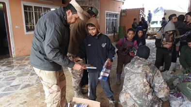 Iraqi army and team giving out clothes and picture books for the children.
