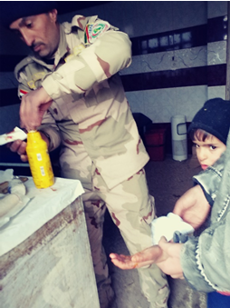 Iraqi army taking care of a little boy who was hit with shrapnel.