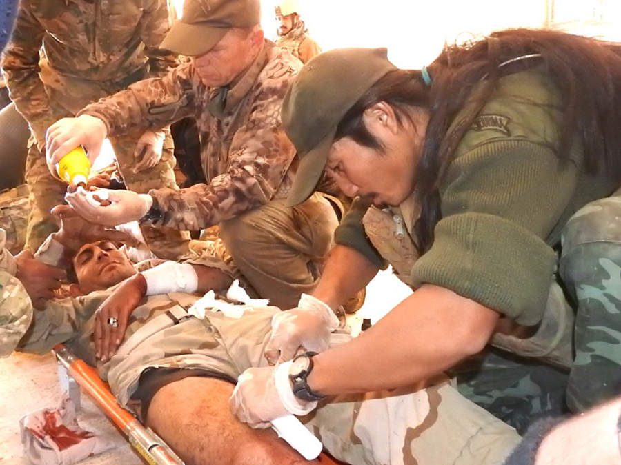 Joseph, an FBR medic, works alongside Iraqi soldiers and medics to stabilize a patient.