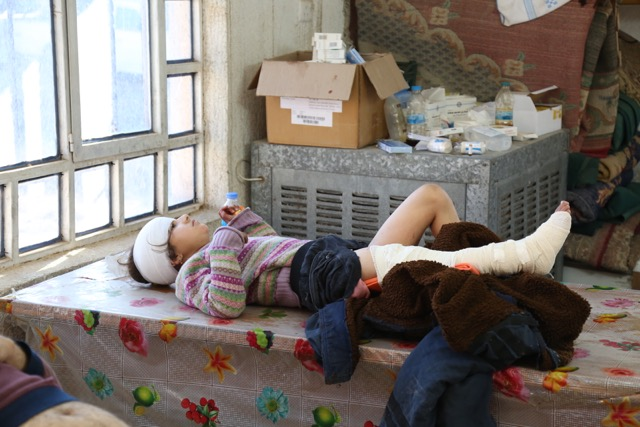 A young girl hit by mortar shrapnel waits for an ambulance to take her to hospital
