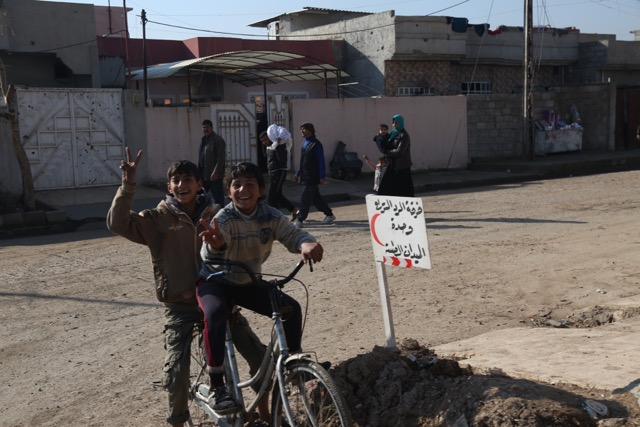Children give us the victory sign, next to a sign pointing to the Iraqi Army clinic