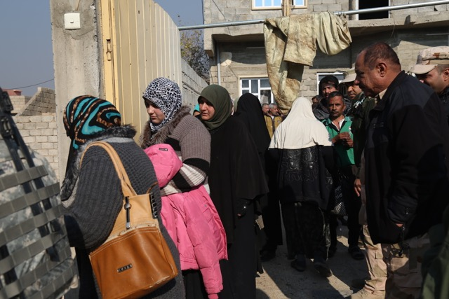 Families fleeing the city line up to receive food