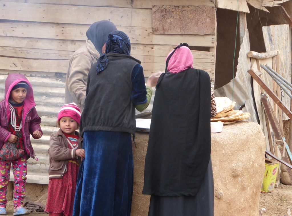 Families make bread in newly liberated neighborhood of Mosul.