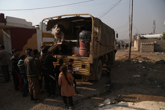 Soldiers handing out food to the residents from the back of their truck
