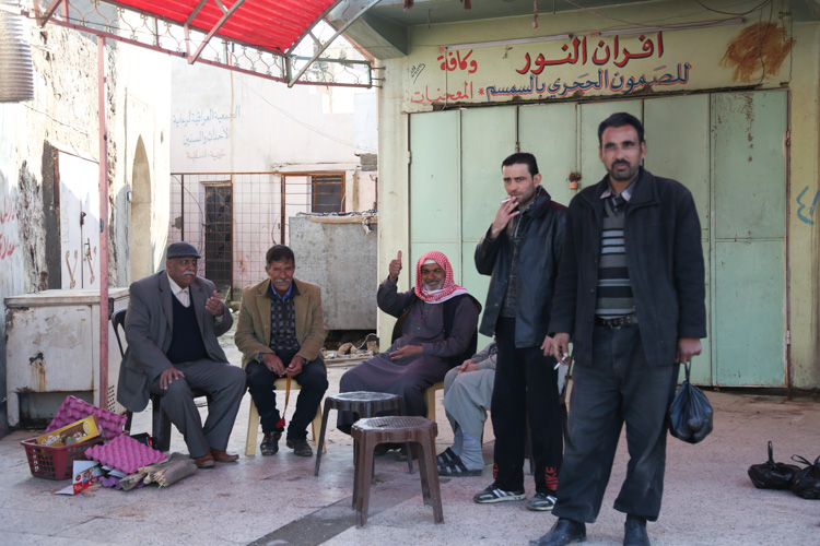 Locals sitting near market drinking tea and smoking