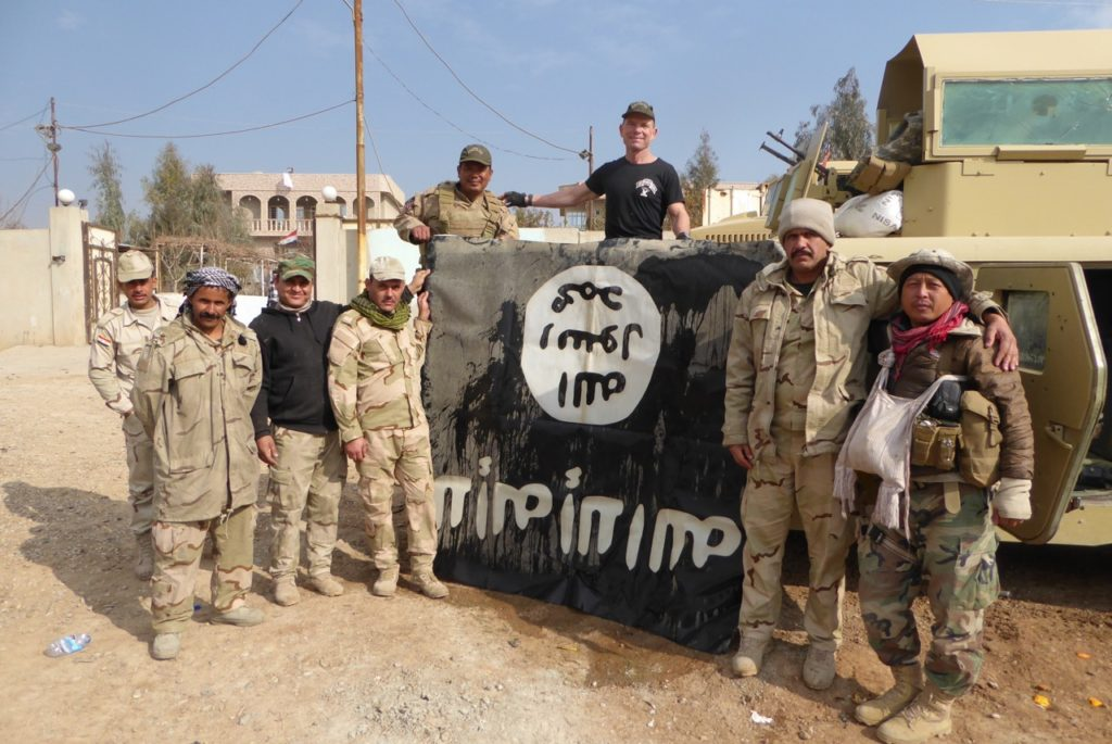 Eliya (far right) with ISIS flag our team captured outside of Mosul