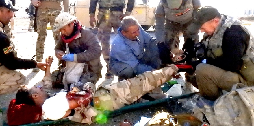 Eliya, medic from Burma, and I treat wounded Iraqi soldier in northeast Mosul