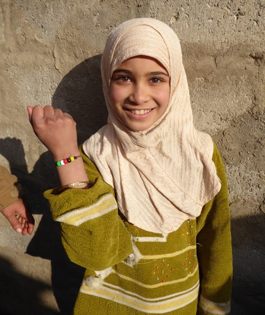 Young girl newly freed from ISIS at a children's program with a bracelet that symbolizes God's love