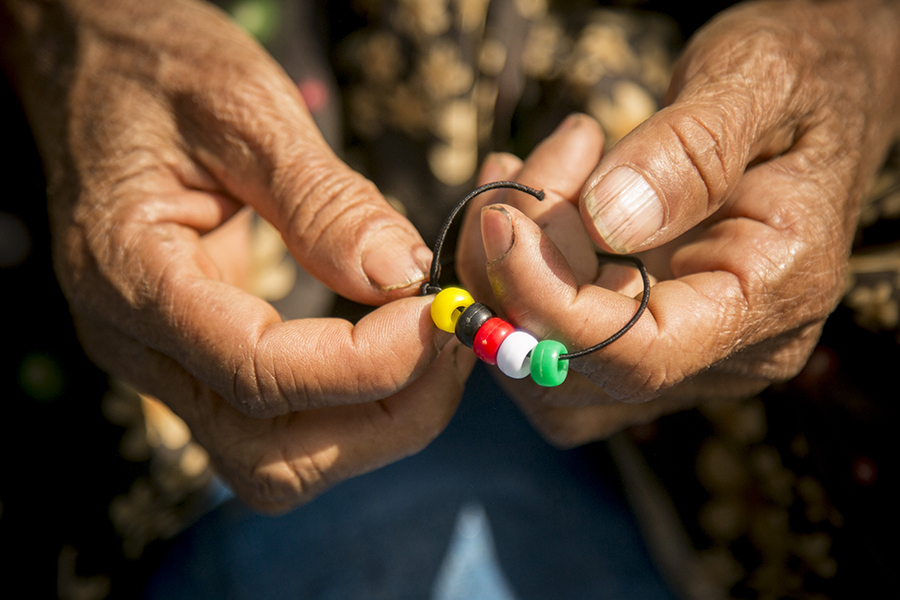 The weathered hands of an opium farmer hold a bracelet with colored beads representing the Christian story of forgiveness and hope, given to her during a Good Life Program for women and children organized during a relief mission to northern Shan State, Burma. (February 2015)