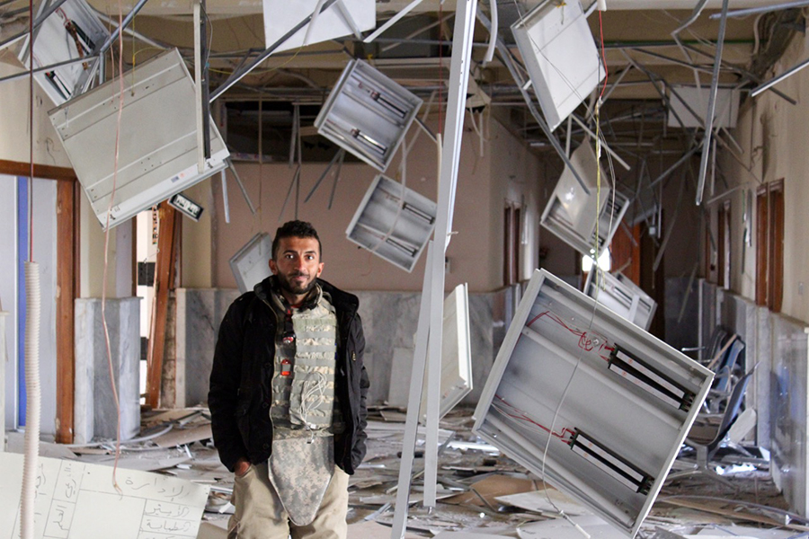 Shaheen in the ruins of the outpatient building at Salam Hospital. Photo courtesy of Riley.