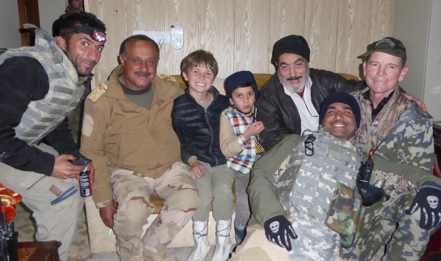 In January 2017, Shaheen (far left) help facilitate the return of a young Yazidi boy (center) to his family after being sold to an Arab family in Mosul.