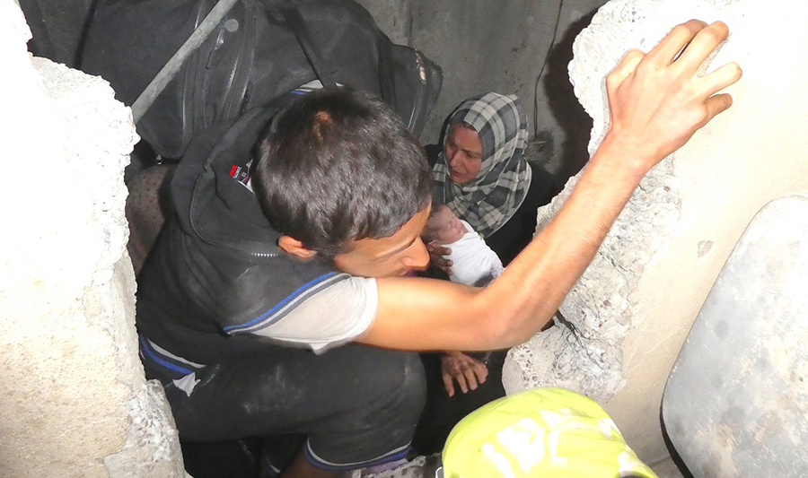Families crawling through holes in the walls to escape ISIS.