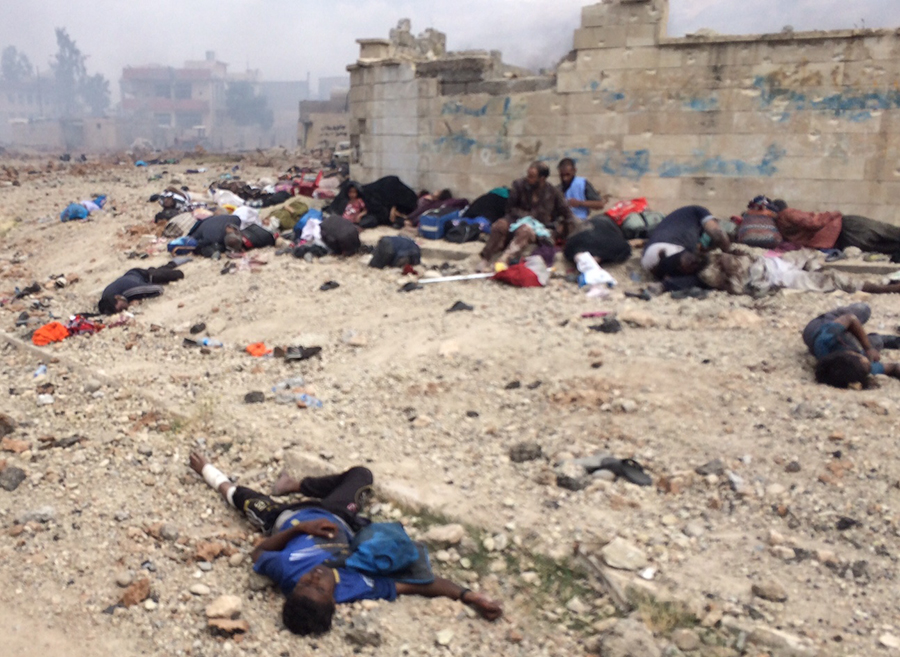 Those still living sit among the dead while waiting for help and surrounded by ISIS fire.