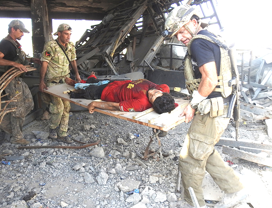 Dave Eubank and a member of the Iraqi Army carry a civilian to safety.