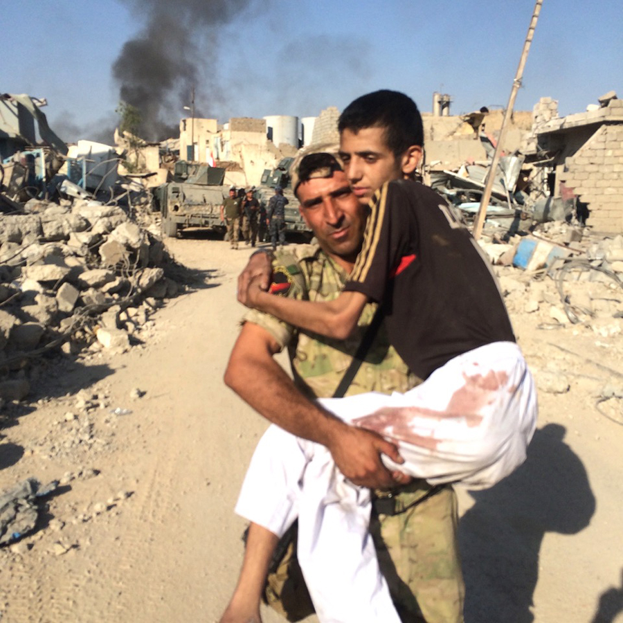 A member of the Iraqi Army carries a civilian to safety.