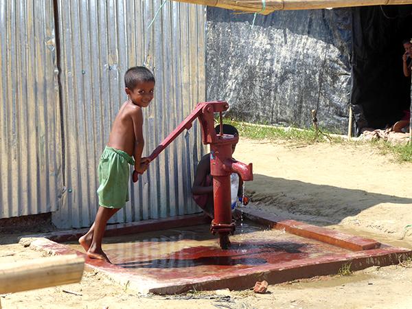 An einer angelegten Grundwasserpumpe besorgt dieser Junge Wasser für seine Familie.