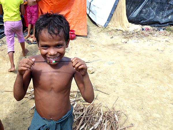 A boy holds up his new GLC bracelet.