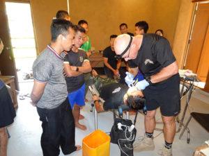 Shannon demonstrating dental procedures to JSMK medics as he fills a tooth.