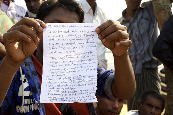 A Rohingya man holds up his written statement that outlines who they are and what they need to be able to return to Burma.