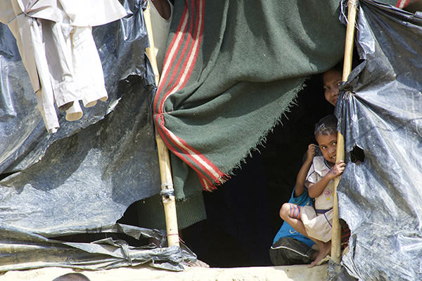 A Rohingya family peeks out of their temporary housing in one of Bangladesh's many refugee camps.