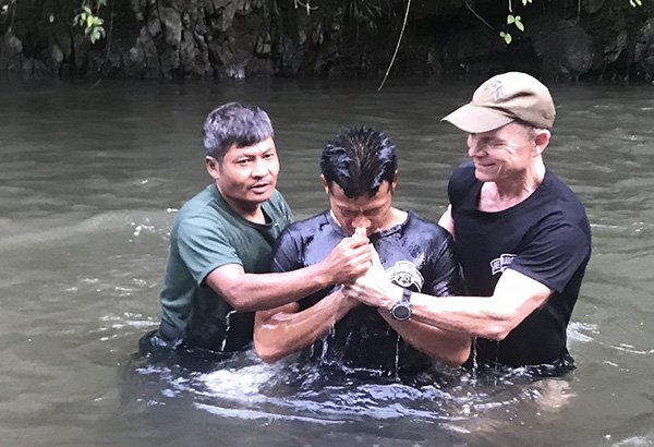 Kwee Po, center, being baptized by FBR Chaplain Monkey (left) and Dave Eubank (right).