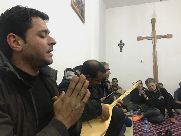 New Syrian Christians sing a prayer with traditional Kurdish guitar.