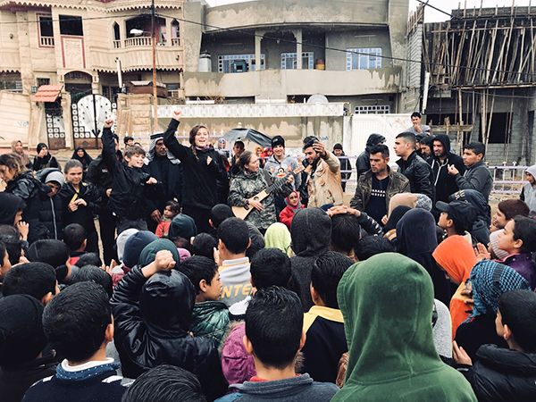 The team sings for families at a new playground in Mosul.