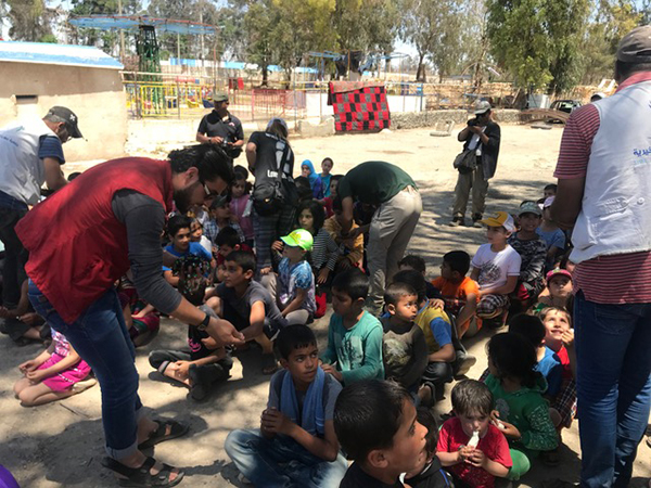 Local NGO workers help us hand out Good Life Club bracelets at the Tabqa program.