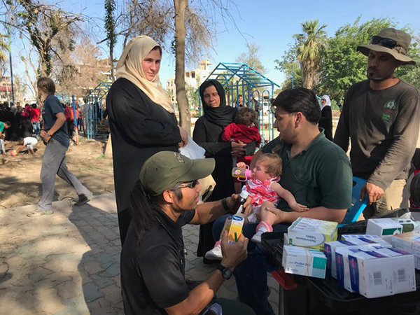 Karen medic Joseph giving medicine to families at the makeshift clinic in the park, Raqqa.