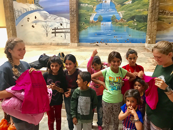 Suu and Sahale give out Reload Love t-shirts to Yezidi kids.