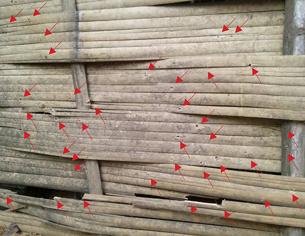 Larger shrapnel impacts are marked in red. The impacts near the bottom of the wall blew in bamboo panels.