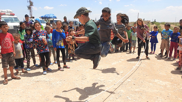 Pete jump ropes with Arab children near Menbij during a Good Life Club program