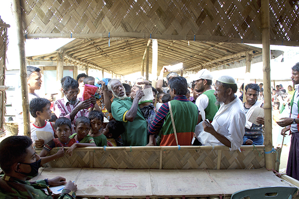 Rohingya men jostle for a spot at the front of a line during a distribution in one of the many refugee camps.