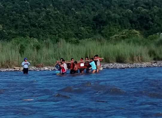 The burial party is forced to ford the river with Mr. Khwe Mana's coffin.
