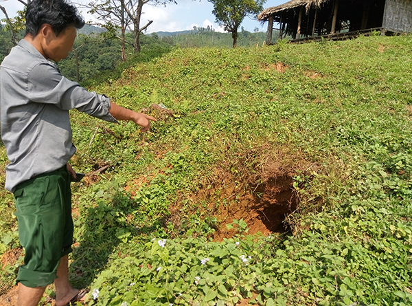 A villager points to where a bomb landed in Kachin State.