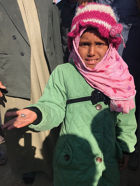 Near Hajin, a girl holds out the ISIS bullet that wounded her.