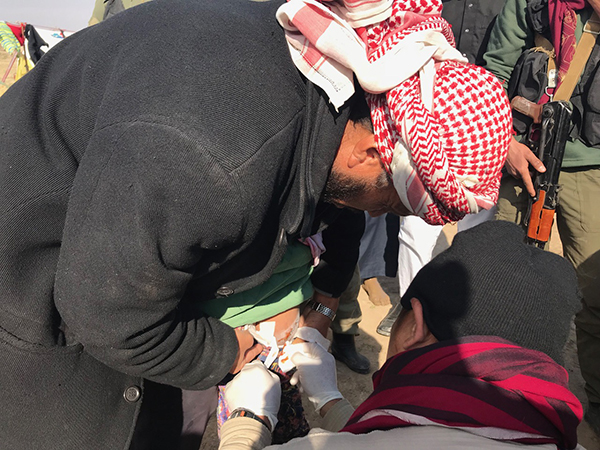 A Karen FBR medic, Eliya, treats the wounded girl.