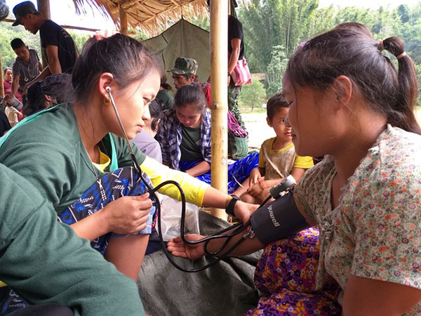 A new medic treats patient at the field clinic during the program.