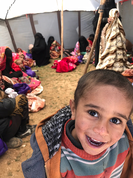 A child who fled Baghuz, now happy in a tent.