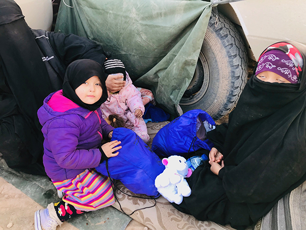 A former ISIS family finds shelter from the wind behind our trucks.
