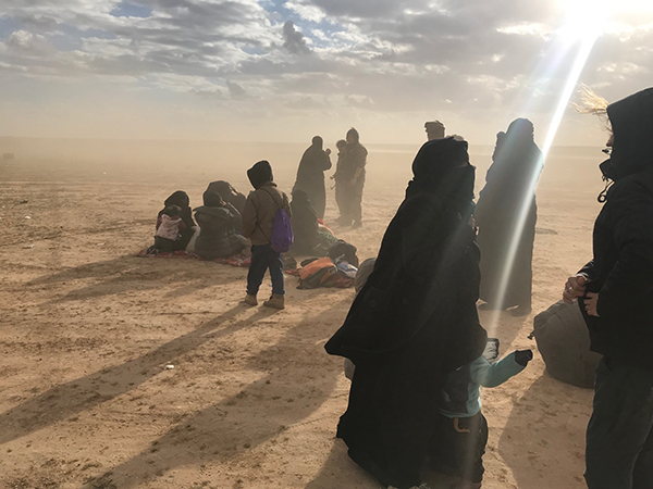 The families are met with dust and freezing wind as they flee ISIS and wait for transport.
