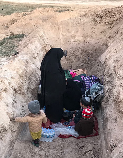 A family takes shelter in a ditch after fleeing.