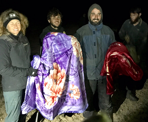 Karen gives blankets to men who recently fled ISIS stronghold.