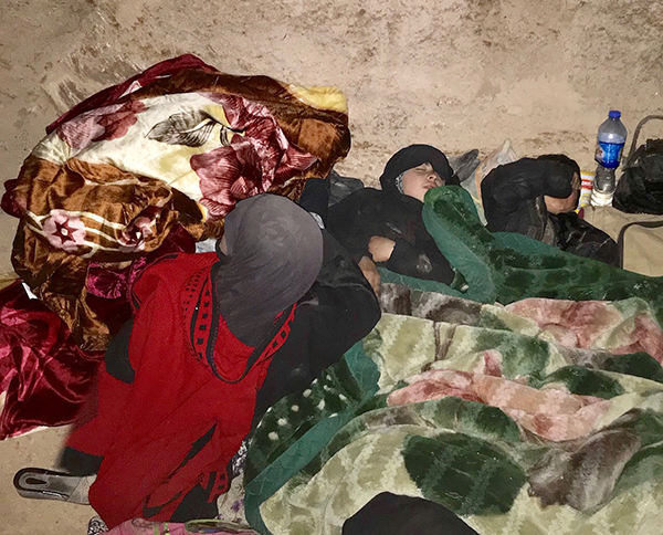 A family sleeping under their new blankets.